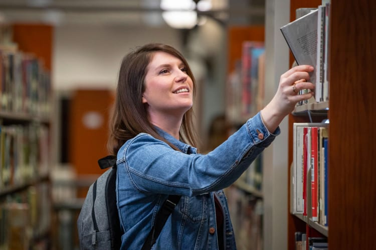 Athens State student pulling book from a shelf