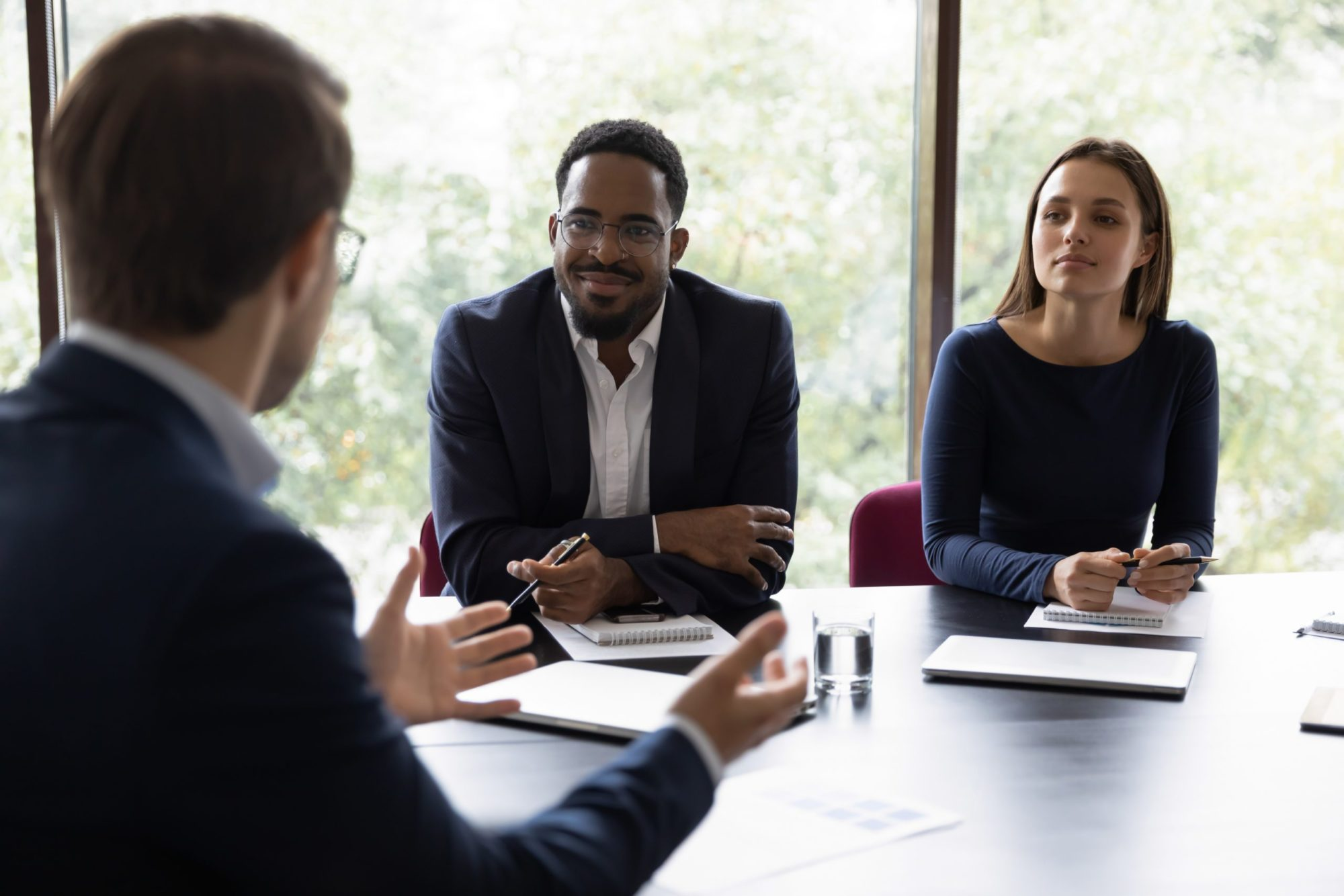 Business leaders meet around a conference table.