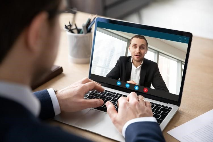 A human resource manager interviews a job candidate in an online meeting.
