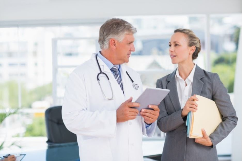 A healthcare administrator talks with a physician.