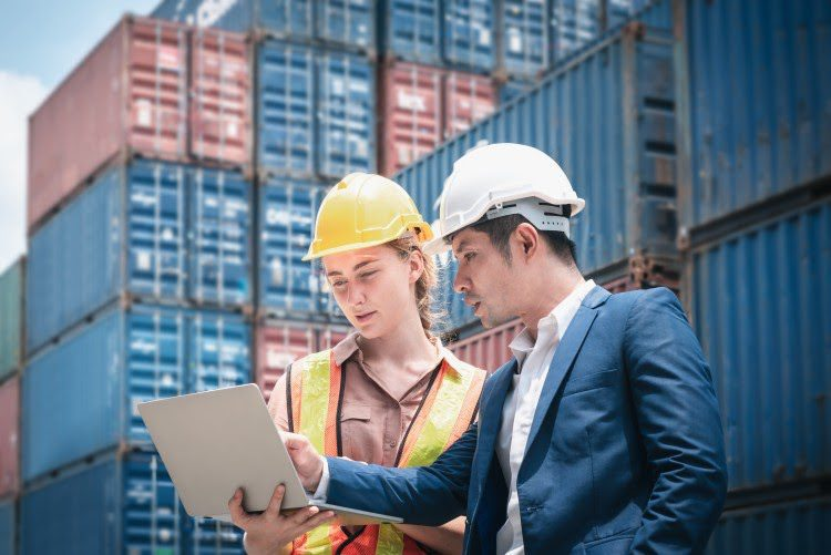 Two supply chain managers at a port ship loading dock are viewing a shipping schedule on a laptop.